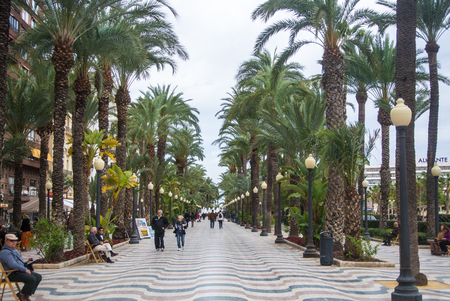 ALICANTE, SPAIN - FEBRUARY 12, 2016: Explanada de Espa a, a famous promenade of Alicante, lanterns, palms and walking and relaxing people, Alicante, Spain.