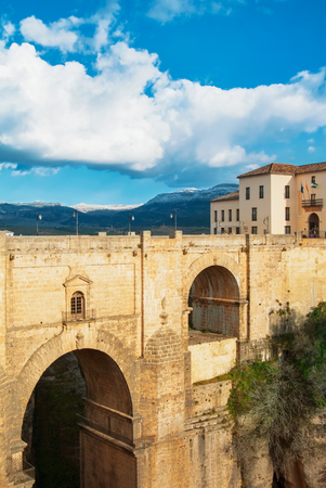 RONDA, SPAIN - FEBRUARY 04, 2014: A view to famous New Bridge (Puente Nuevo), houses standing near the bridge and mountains in Ronda, one of the most famous white villages (pueblos blancos) in Malag