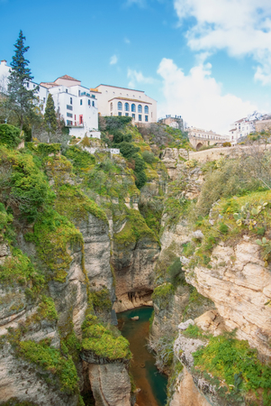 A view to Guadalevin river at El Tajo Gorge Canyon and traditional andalusian houses at the cliff in Ronda, a famous white village (pueblo blanco) in Malaga province, Andalusia, Spain.