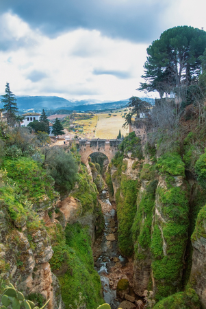 A view to Guadalevin river at El Tajo Gorge Canyon, Old Bridge (Puente Viejo) and mountains in Ronda, one of the most famous white villages (pueblos blancos) in Malaga province, Andalusia, Spain.