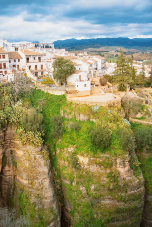 A view to El Tajo Gorge Canyon, white traditional andalusian houses and mountains in Ronda, one of the most famous white villages (pueblos blancos) in Malaga province, Andalusia, Spain.