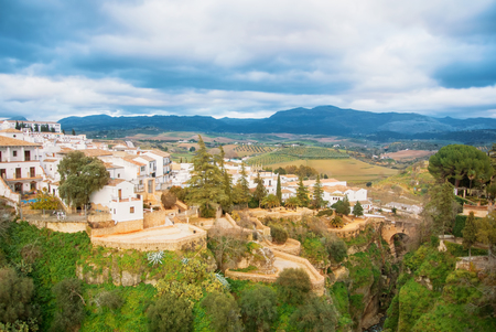 A view to El Tajo Gorge Canyon, Old Bridge (Puente Viejo) and mountains in Ronda, one of the most famous white villages (pueblos blancos) in Malaga province, Andalusia, Spain.