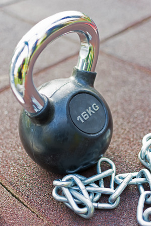 Kettlebell With Handle and Chains Background. Fitness Exercise Equipment for Street Workout.