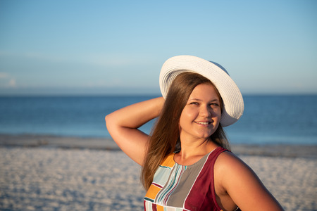 Photo pour Portrait of a young  beautiful carefree woman walking on sunny beach wearing dress and hat - image libre de droit