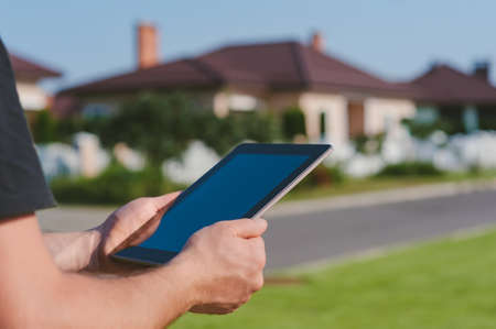Photo pour A tablet in the hands of a man against the backdrop of a private house - image libre de droit