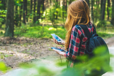 Photo pour Power bank and smartphone in the hands of a girl with red hair in a shirt in a cage with a black backpack, on the background of a forest road - image libre de droit