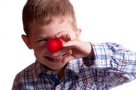 A little boy with a clown nose on a white background