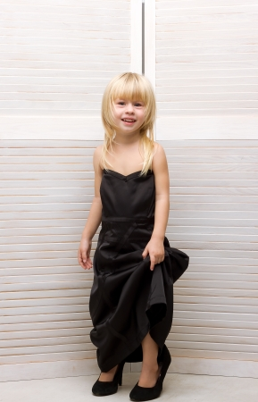 Girl 3 years old in my mother's black dress and high heels