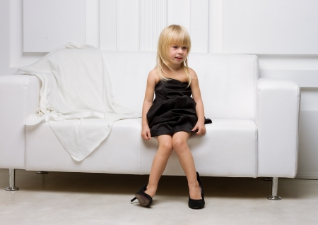 Photo for Girl 3 years old in her mother's high heels sitting on a white sofa - Royalty Free Image