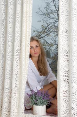 young beautiful woman enjoying her morning near big window in hotel / room