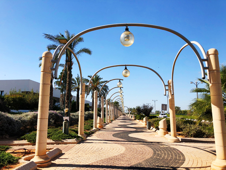 RISHON LE ZION, ISRAEL -December 4, 2018: Street light and palm trees along sidewalk against blue sky  in Rishon Le Zion, Israel.
