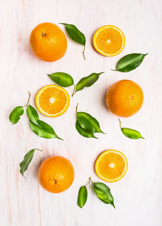 Orange fruits composition with green leaves and slice on white wooden background, top view