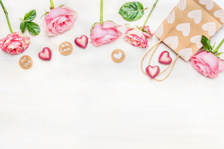 Photo pour Pink roses with chocolate heart, shopping bag and round sign with message for you and with love on light background, top view.  Valentine Day or Birthday greeting card. Border. - image libre de droit