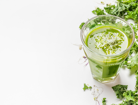 Healthy green smoothie drink in glass with kale ingredients on white wooden background, close up. Detox nutrition and cleaning food concept.