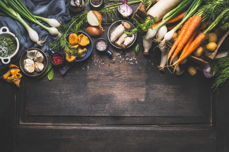 Organic harvest Vegetables from garden and  forest mushrooms. Vegetarian ingredients  for cooking on dark rustic wooden background, top view, border