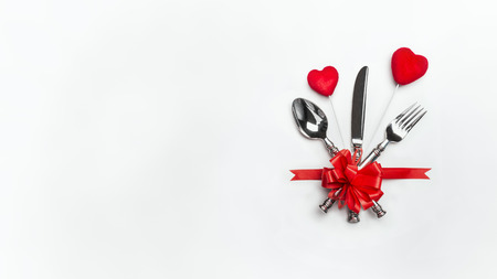 Photo pour Festive table with red bow, cutlery and two hearts on white background, banner. Layout for Valentines day dinner invitation or menu, banquet, celebration, event - image libre de droit