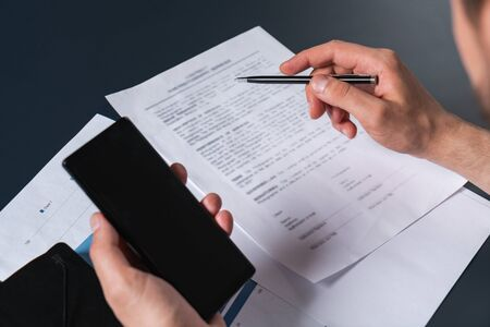 A man signing the contract double checking details in cell phone . The concept of entering into legal power to take liabilities. Casual wearing.