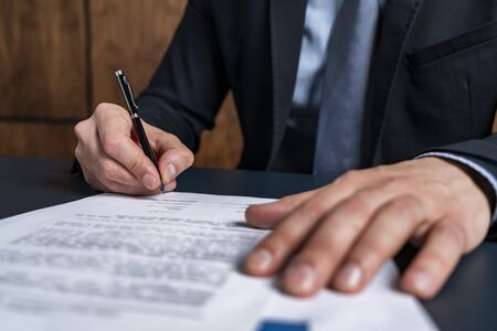 Photo pour A man broker signing the mortgage contract at the real property agent office. The concept of entering into legal power to take liabilities. - image libre de droit