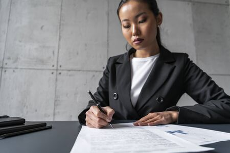 Photo pour Concentrated young Asian businesswoman signing contract in loft office. Concept of management and paperwork - image libre de droit