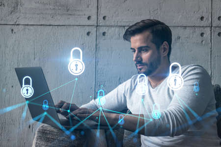 Photo for A serious caucasian programmer in casual wears, using laptop to develop a new security system to protect data. Double exposure. IT lock hologram icon. - Royalty Free Image