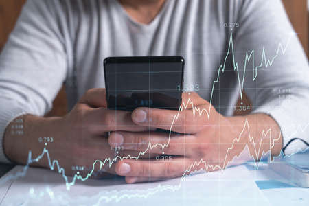 Photo pour Trader holding in the hands a smart phone and researching stock market to proceed right investment solutions. Internet trading and wealth management concept. Hologram Forex chart over close up shot. - image libre de droit