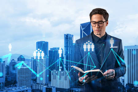 Photo pour Handsome eastern HR director at international company is looking into personal organizer to plan business meeting to recruit highly qualified specialists. Social media hologram icons over Kuala Lumpur - image libre de droit