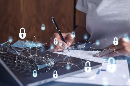Photo pour A businesswoman in casual wear signing the contract to prevent probability of risks in cyber security. Padlock Hologram icons over the working desk. - image libre de droit