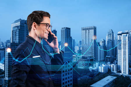 Photo pour Handsome eastern analyst pensively processing conference call by phone to find financial solution for venture capital project. Hologram chart over Bangkok city background - image libre de droit