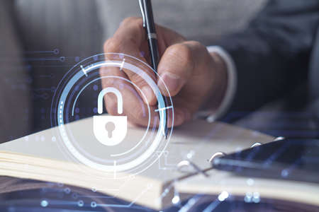 Photo pour Programmer is taking notes of clients needs to protect cyber security from hacker attacks and save clients confidential data. Using smart phone. Padlock Hologram icons. Formal wear - image libre de droit