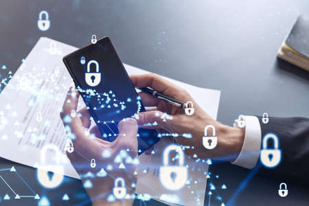 Photo pour A businessman in formal wear reading the contract to prevent probability of risks in cyber security and checking details in the phone. Padlock Hologram icons over the working desk. - image libre de droit