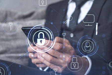 Photo pour A programmer is browsing the Internet in smart phone to protect a cyber security from hacker attacks and save clients confidential data. Padlock Hologram icons over the typing hands. Formal wear. - image libre de droit