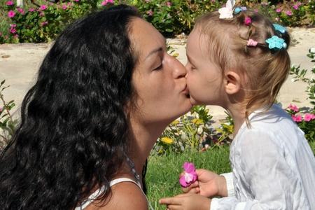 Foto de A woman with long black curly hair kisses her daughter on a sunny day. - Imagen libre de derechos