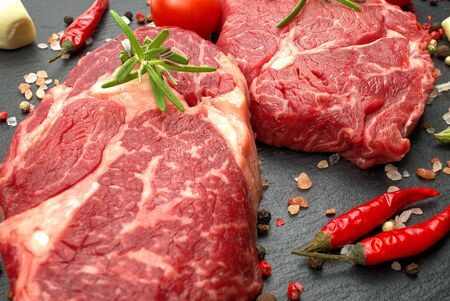 Photo for Raw rib eye steak with spices and vegetables. Ingredients for restaurant meal. Fresh meat, salt, rosemary, thyme, chilli, cherry tomatoes, garlic on black stone. Food background. - Royalty Free Image