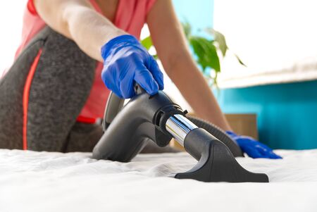 Photo pour Vacuuming bed. Domestic home cleaning concept. Textile sofa chemical cleaning. Upholstered furniture. Early spring cleaning or regular clean up. Cleaning Service conceptatHome, apartments, hotels. - image libre de droit