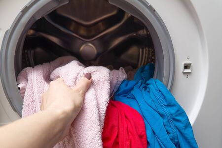 Photo pour girl takes out the laundry from the washing machine. woman puts clothes in a washing machine. - image libre de droit