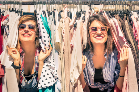 Photo pour Young beautiful women at the weekly cloth market - Best friends sharing free time having fun and shopping in the old town in a sunny day - Girlfriends enjoying everyday life moments - image libre de droit