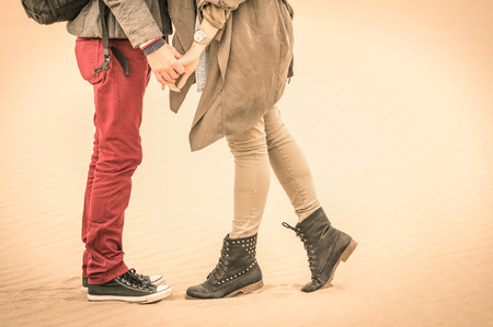 Concept of love in autumn - Couple of young lovers kissing outdoors with closeup on legs and shoes - Desaturated nostalgic filtered look