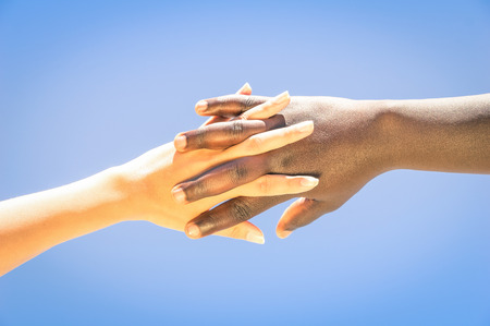 Interracial human hands crossing fingers for friendship and love - Concept of peace and unity against racism