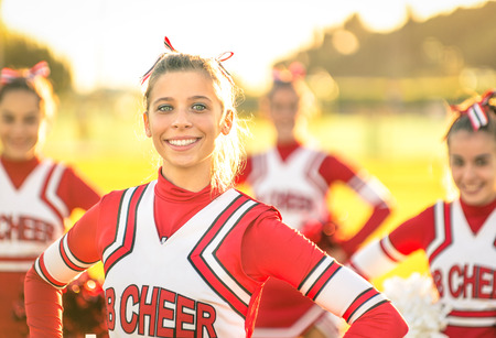 Portrait of an happy young cheerleader in action outdoors - Group of girlfriends during cheerleading sport training at high school