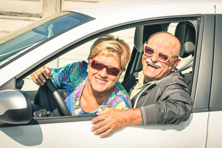 Happy senior couple ready for driving a car on a journey trip - Concept of joyful active elderly lifestyle with man and woman enjoying their best years