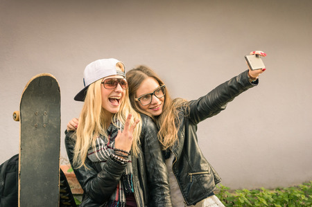 Photo pour Hipster girlfriends taking a selfie in urban city context - Concept of friendship and fun with new trends and technology - Best friends eternalizing the moment with modern smartphone - image libre de droit