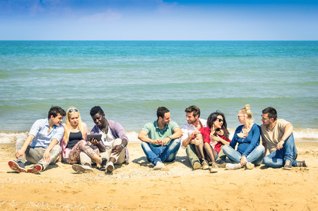 roup of international best friends sitting at beach talking with each other - Concept of multi cultural friendship against racism - Interaction with new technologies tablet and contact with nature