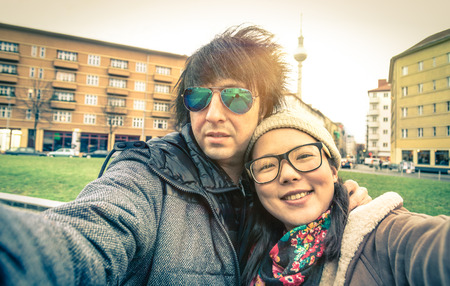 Hipster couple of tourists taking a selfie in Berlin City - Multiracial concept of friendship and fun with new trends and technology - Asian girl with alternative young fashion handsome guy