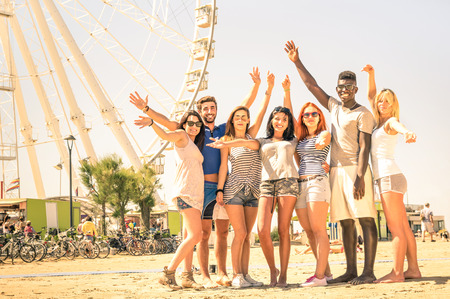 Group of multiracial happy friends cheering at ferris wheel - International concept of happiness and multi ethnic friendship all together against racism for peace and fun - Warm nostalgic filter