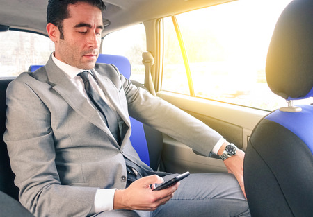 Young handsome businessman sitting in taxi cab while texting sms with smartphone - Business concept with modern man using smart phone - Soft vintage editing with artificial sunlight from the window