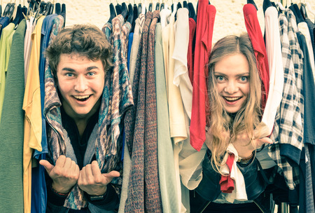 Young hipster couple in love at the weekly cloth market - Best friends sharing free time having fun and shopping in the old town - Lovers enjoying everyday life moments on a vintage filtered look