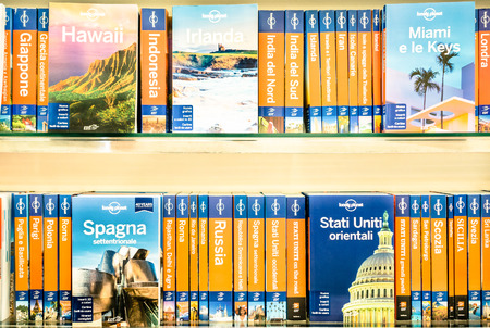 RIMINI, ITALY - MARCH 15, 2014: Lonely Planet volumes on a shelf. The famous company is the largest travel guide book publisher in the world and is owned by the american billionaire Brad Kelley