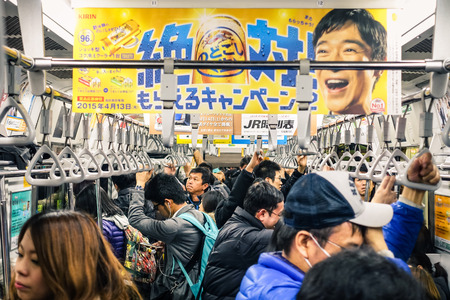 TOKYO - FEBRUARY 26, 2015: full train during rush hour in the underground. The combined subway network of the Tokyo and Toei metros counts 290 stations and 13 lines. Crowded cropped composition .
