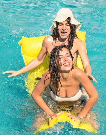 Best friends in bikini enjoying time together outdoors in swimming pool - Concept of freedom and happiness with two girlfriends having fun in the summer