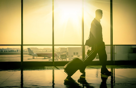 Business man at the international airport with travel suitcase moving to terminal gate